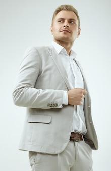 Beau modèle d'homme blond dans un costume gris fashion en studio