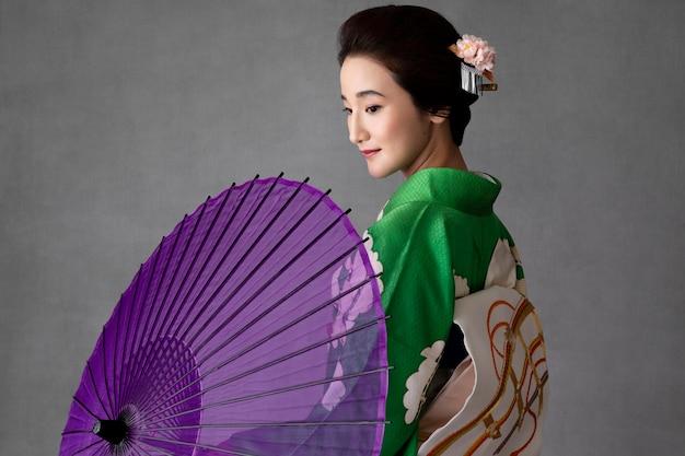 Beau modèle japonais avec un parapluie violet