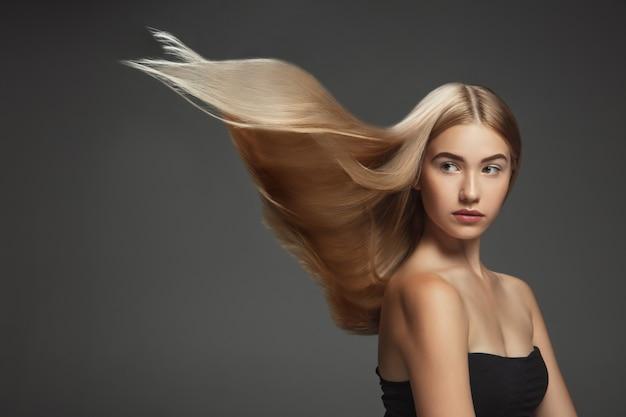 Beau modèle avec de longs cheveux blonds lisses et volants isolés sur un mur de studio gris foncé