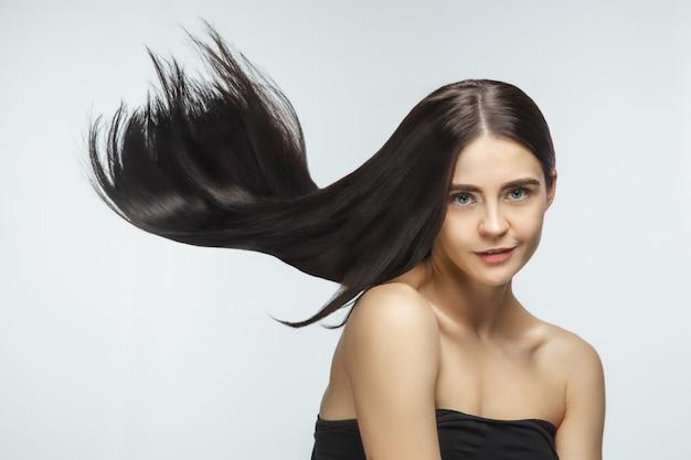 Beau modèle avec de longs cheveux bruns lisses et volants isolés sur fond de studio blanc.