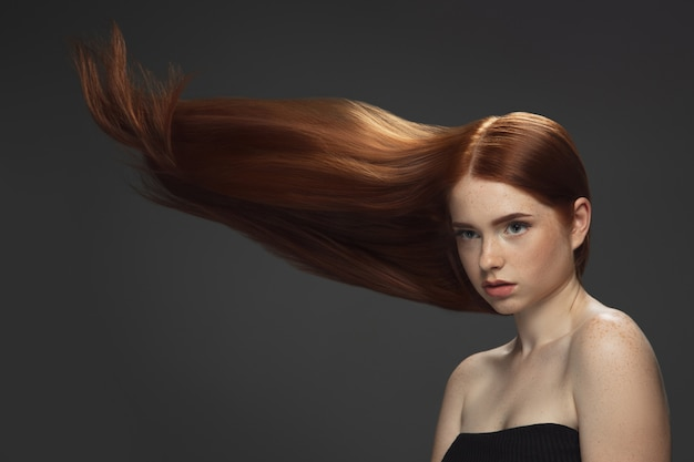 Beau modèle avec de longs cheveux roux lisses et volants isolés sur fond sombre