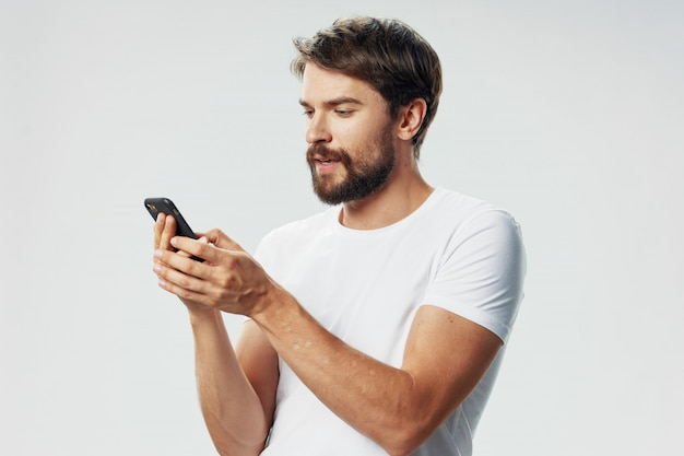 Beau modèle masculin avec barbe avec un téléphone qui pose en studio