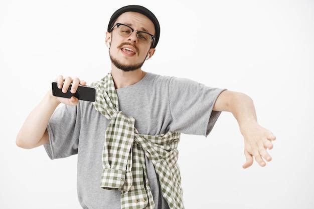 Beau modèle masculin charismatique et détendu avec barbe dans des lunettes et bonnet hipster dansant avec les mains écartées, expression insouciante écoutant de la musique dans des écouteurs sans fil tenant un smartphone
