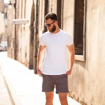 Beau modèle masculin hipster avec barbe portant un t-shirt blanc blanc avec un espace pour votre logo ou design dans un style urbain décontracté