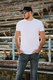 Beau modèle masculin hipster avec barbe portant un t-shirt blanc et une casquette de baseball avec un espace pour votre logo ou votre design dans un style urbain décontracté