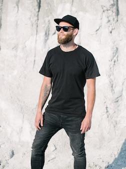 Beau modèle masculin hipster avec barbe portant un t-shirt blanc noir avec un espace pour votre logo ou design dans un style urbain décontracté