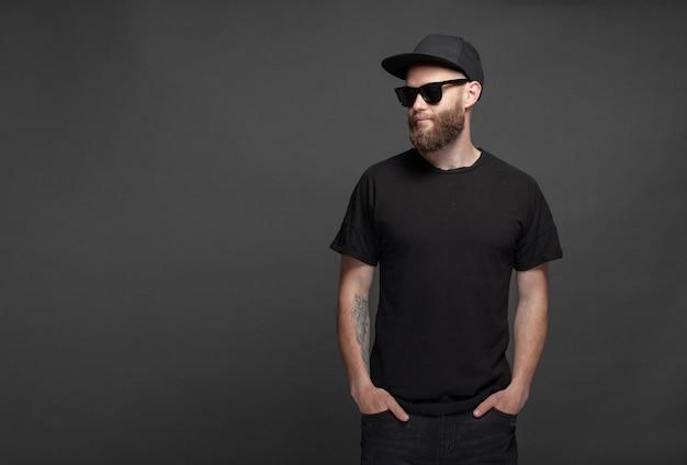 Beau modèle masculin hipster avec barbe portant un t-shirt blanc noir avec un espace pour votre logo ou votre design