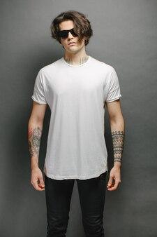Beau modèle masculin hipster avec des lunettes portant un t-shirt blanc et un jean noir avec un espace pour votre logo ou votre design dans un style urbain décontracté
