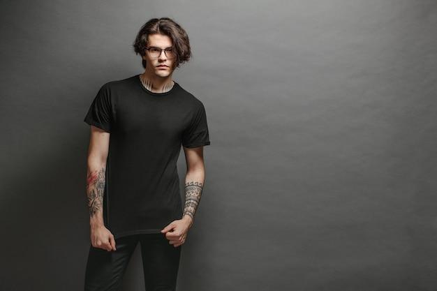 Beau modèle masculin hipster avec des lunettes portant un t-shirt blanc noir et un jean noir avec un espace pour votre logo ou votre design dans un style urbain décontracté