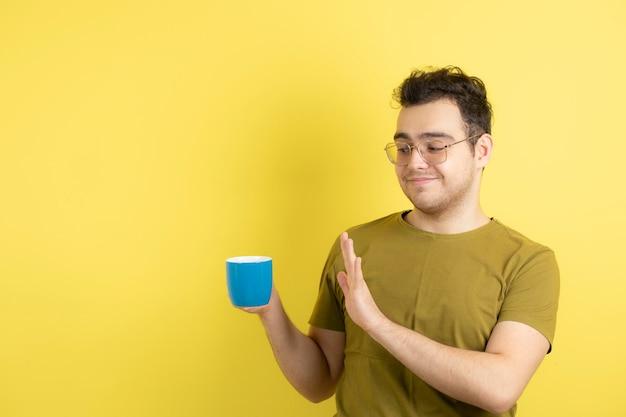 Beau modèle masculin restant à l'écart de la tasse de thé.