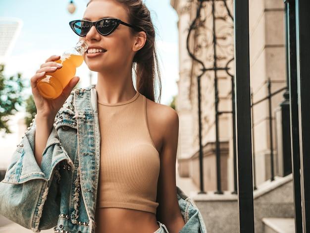 Beau modèle mignon souriant dans des vêtements de veste de jeans hipster d'été posant dans la rue