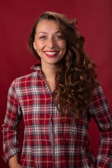 Beau modèle poilu long bouclé souriant en chemise à carreaux posant sur studio rouge