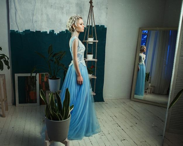 Beau modèle portant une robe bleu clair pose dans un studio