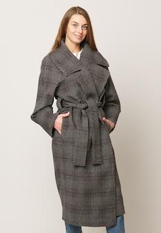 Beau modèle posant dans un long manteau marron sur fond blanc. tourné en studio. concept de publicité de vêtements.