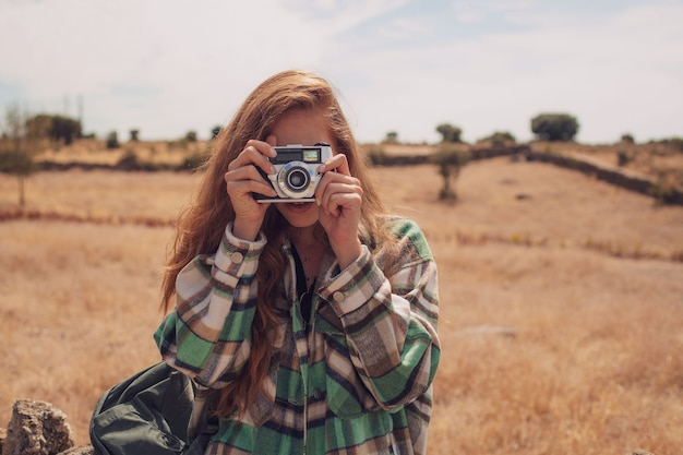 Un beau modèle prend une photo avec un appareil photo analogique