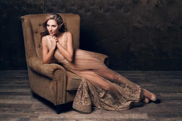 Beau modèle sexy femme en robe de soirée en dentelle brillante posant assis dans une chaise de couleur beige