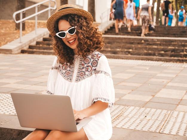 Beau modèle souriant avec coiffure afro curls en robe et chapeau blanc hipster d'été.