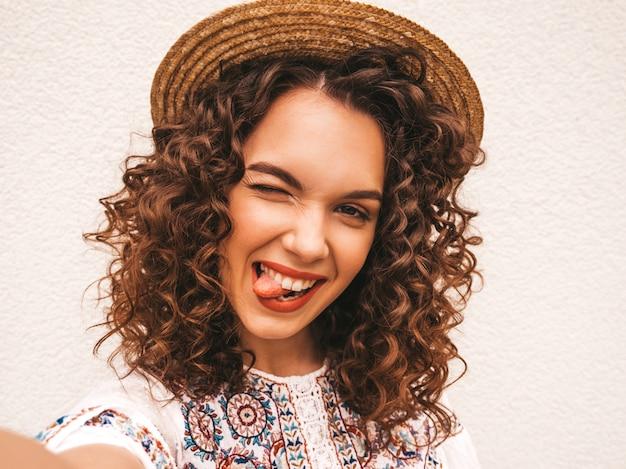 Beau modèle souriant avec une coiffure de boucles afro habillée en robe blanche d'été hipster.
