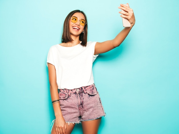 Beau modèle souriant vêtu de vêtements d'été hipster. fille insouciante sexy qui pose en studio près du mur bleu en short jeans. tendance et drôle femme prenant des photos d'autoportrait selfie sur smartphone