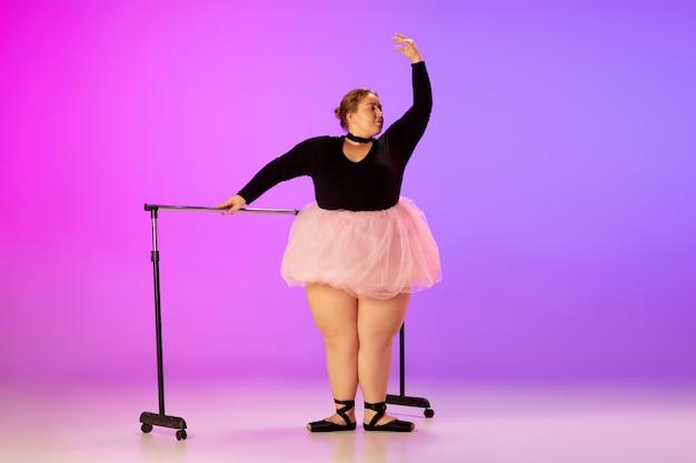 Beau modèle de taille plus caucasien pratiquant la danse de ballet sur un studio violet rose dégradé
