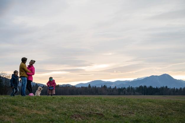 Beau moment en famille avec des parents s'embrassant et des enfants jouant avec leur chien dehors sous le ciel du soir dans une belle prairie.