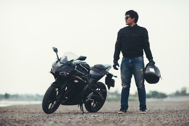 Beau motard avec casque dans les mains de la moto