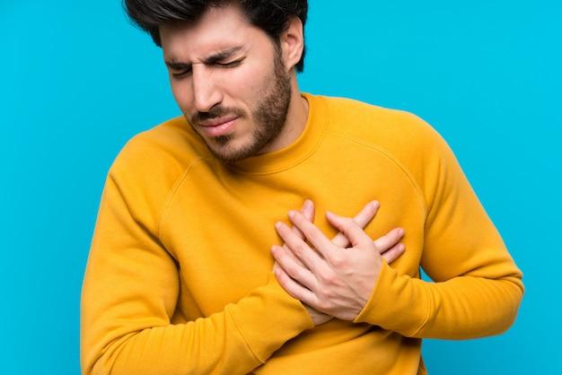Beau sur mur bleu isolé ayant une douleur au coeur
