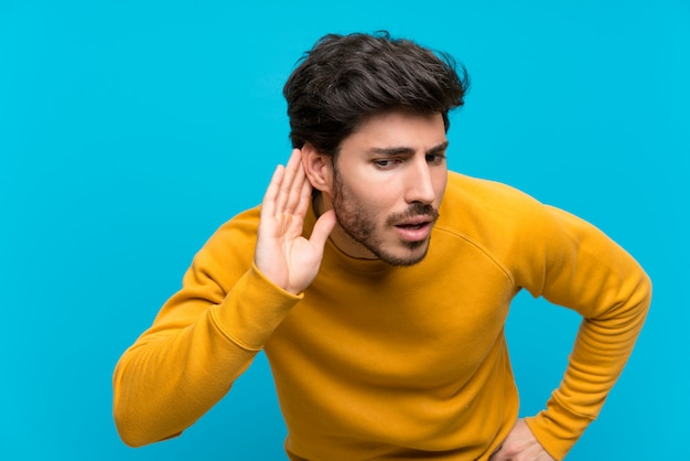 Beau sur mur bleu isolé, écouter quelque chose en mettant la main sur l'oreille