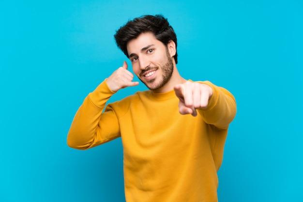 Beau sur mur bleu isolé, faisant un geste de téléphone et devant pointant