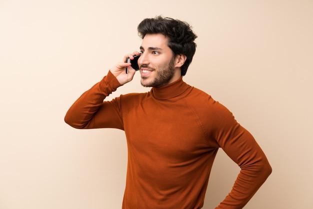 Beau sur un mur isolé, gardant une conversation avec le téléphone mobile