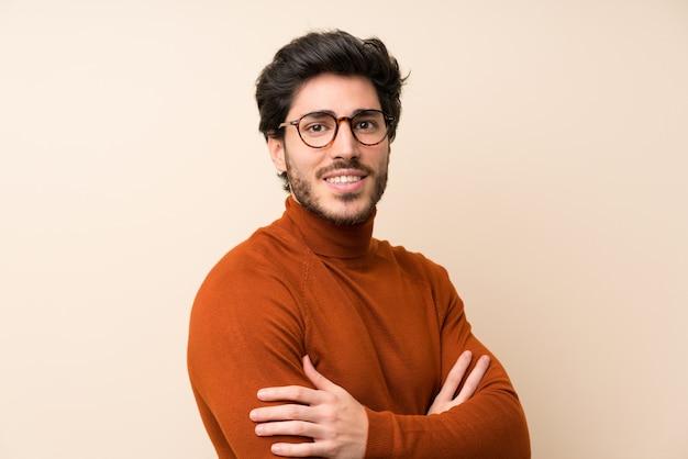 Beau sur un mur isolé avec des lunettes et souriant
