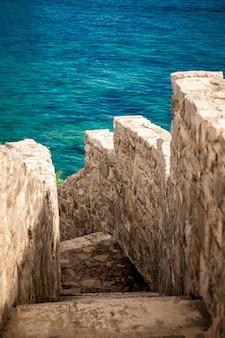 Beau mur en pierre antique avec des escaliers menant à la mer bleue