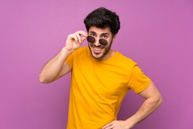 Beau sur un mur violet isolé avec des lunettes et heureux