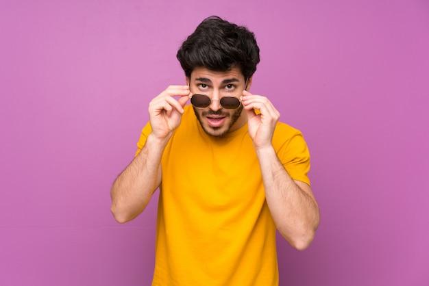 Beau mur violet isolé avec des lunettes et surpris
