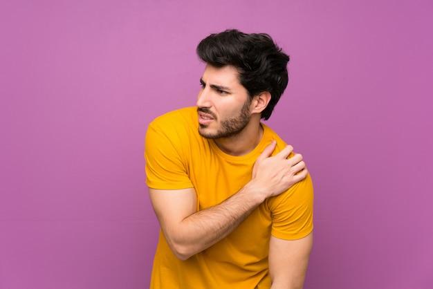 Beau mur violet isolé souffrant de douleur à l'épaule pour avoir fait un effort