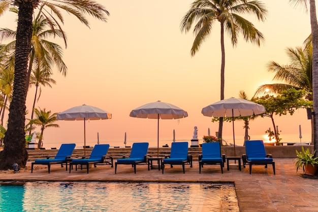 Beau palmier avec chaise parasol piscine dans un hôtel de luxe