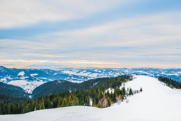 Beau panorama sur les pentes de la montagne avec des sentiers surplombant les collines et les forêts de conifères couvert et givré un soir d'hiver