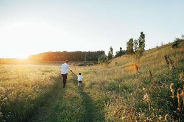 Beau papa avec son petit fils mignon s'amuse et joue sur la pelouse verte.
