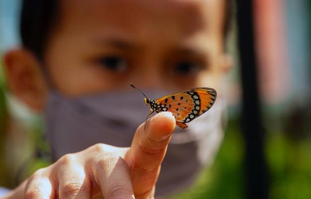 Un beau papillon sur un doigt d'un enfant portant un masque, mise au point sélectionnée