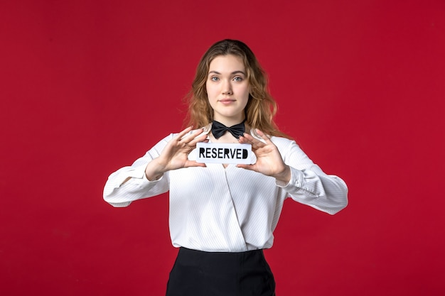 Beau papillon serveur féminin confiant sur le cou et tenant une icône réservée sur fond rouge