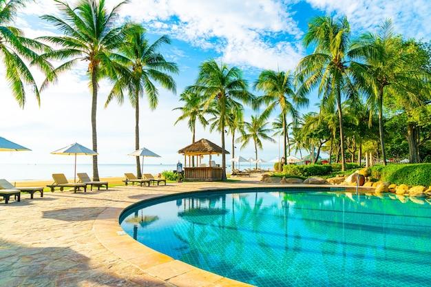 Beau parapluie de luxe et chaise autour de la piscine extérieure dans l'hôtel et la station balnéaire avec cocotier sur ciel bleu - vacances et concept de vacances