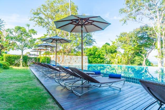 Beau parasol et chaise autour de la piscine dans l'hôtel et la station
