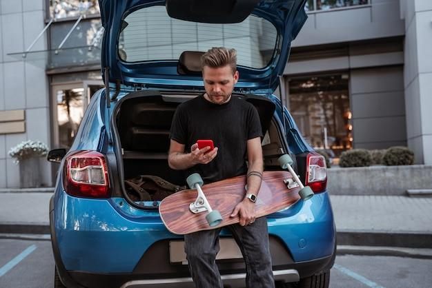 Beau patineur blond tenant un longboard assis sur un parking dans le coffre de la voiture à l'aide d'un smartphone. habitudes urbaines. concept de sport extrême. notion de communication. concept de vie en ville. concept de loisirs en plein air.