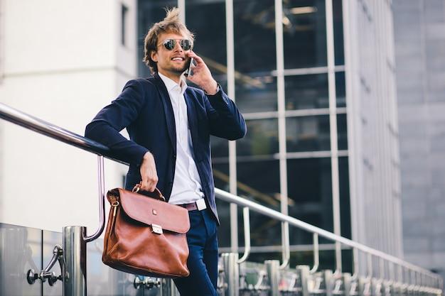 Un beau patron masculin en costume formel et une mallette à la main sourit en parlant au téléphone dans la rue