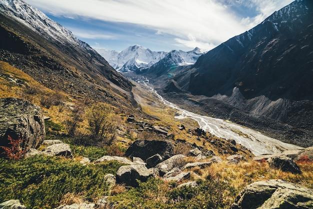 Beau paysage alpin avec de grandes montagnes enneigées et une rivière de montagne avec de nombreux ruisseaux dans la vallée parmi les rochers aux couleurs d'automne au soleil. superbe paysage ensoleillé avec un mur de haute montagne enneigé à l'automne