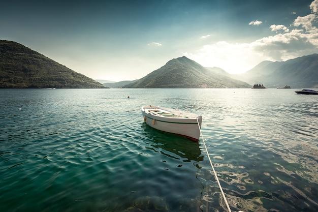 Beau paysage de barque blanche amarrée à la baie entourée de montagnes tôt le matin