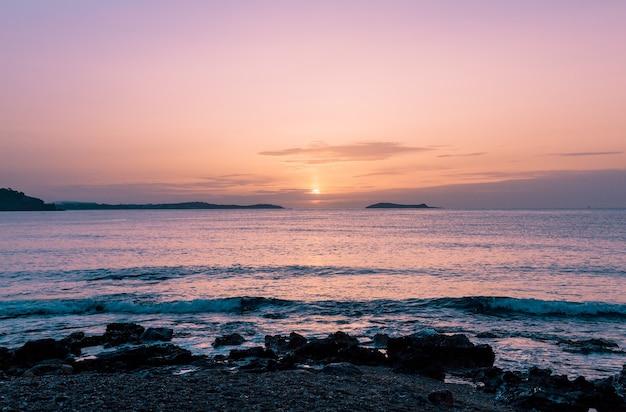 Beau paysage d'un bord de mer rocheux et d'une mer pendant le coucher du soleil