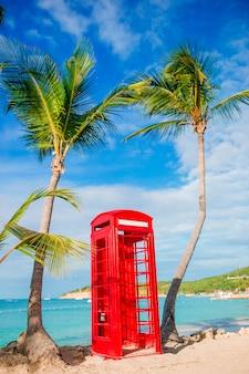 Beau paysage avec une cabine téléphonique classique sur la plage de sable blanc à antigua