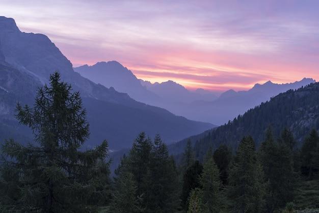 Beau paysage d'une chaîne de montagnes entourée de sapins sous le ciel coucher de soleil