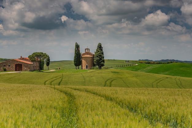 Beau paysage de champs de campagne entourés de collines sous le ciel sombre